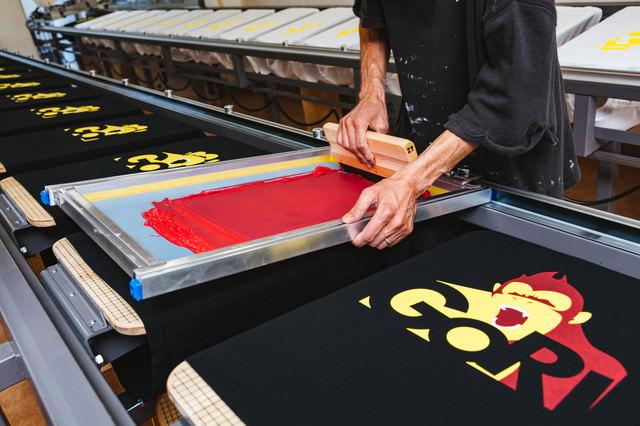 手刷りでTシャツに着色するシルクスクリーン印刷の現場の写真