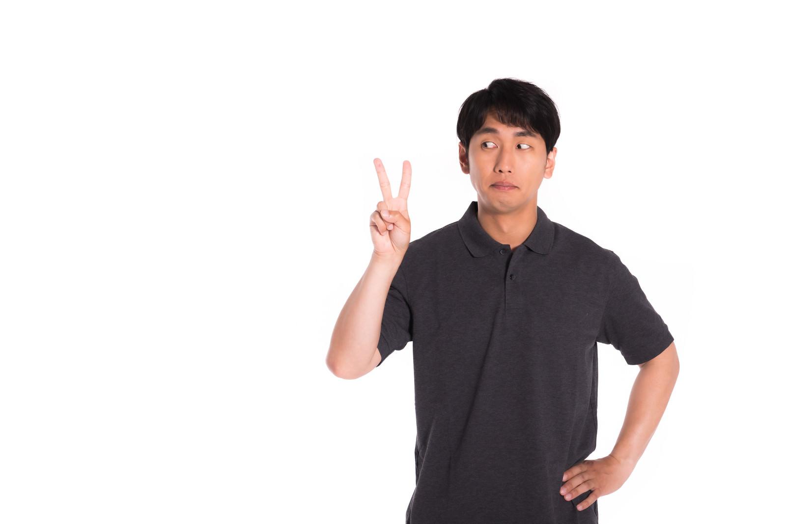 「2本指を見つめる男性」の写真[モデル:大川竜弥]