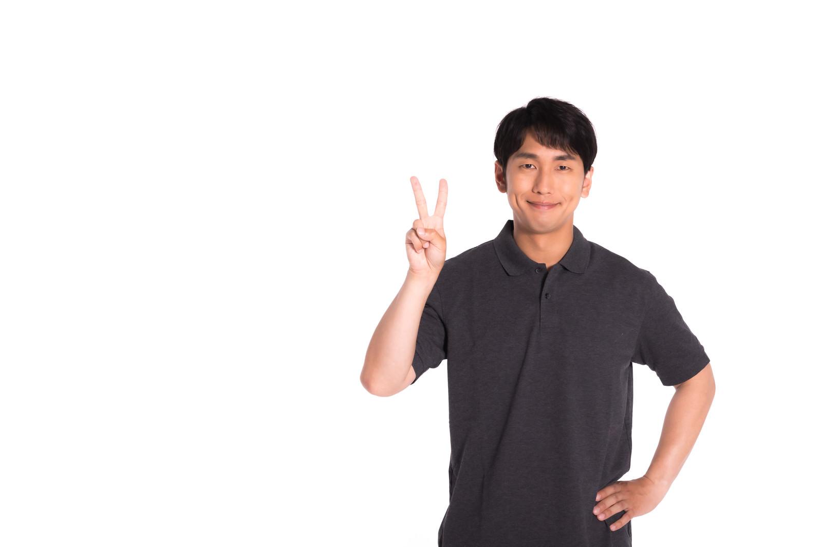 「笑顔でピースサインをする男性」の写真[モデル:大川竜弥]