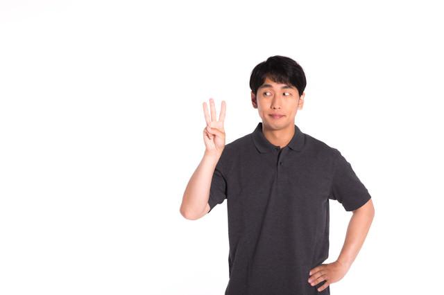 3本指を見つめる男性の写真