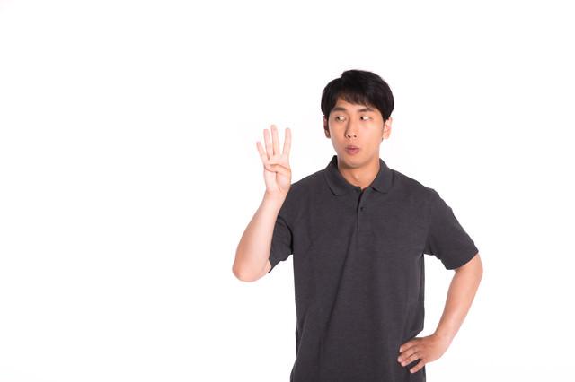 4本指を見つめる男性の写真