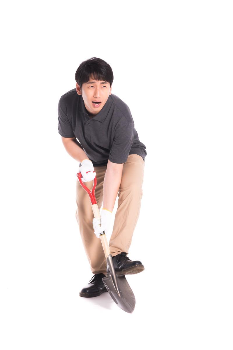 「嫌々ながら穴を掘らされる男性」の写真[モデル:大川竜弥]
