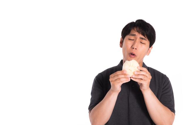 豚まんを食べる男性の写真