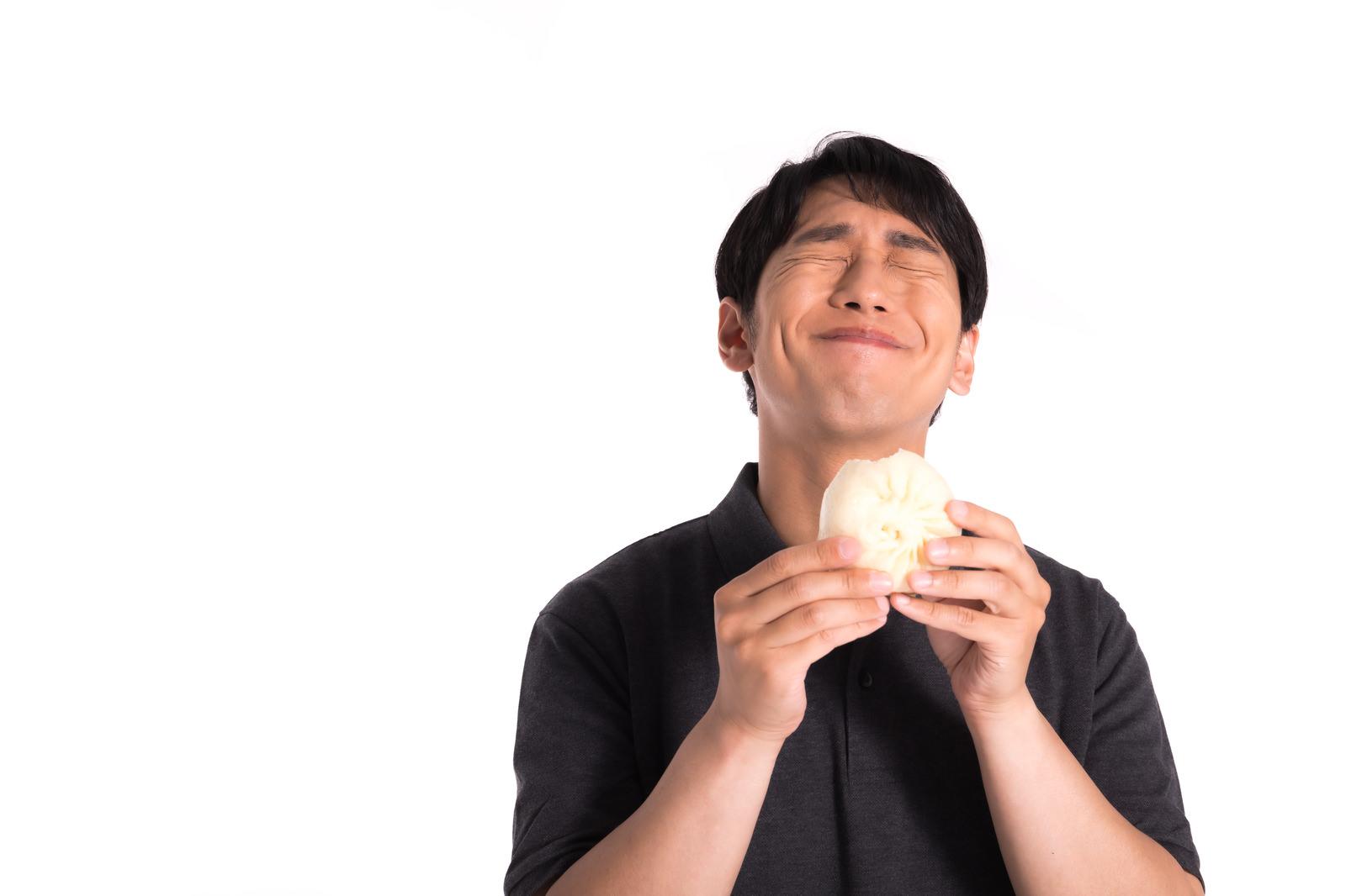 「これぞ求めていた味だと豚まんを食らう」の写真[モデル:大川竜弥]