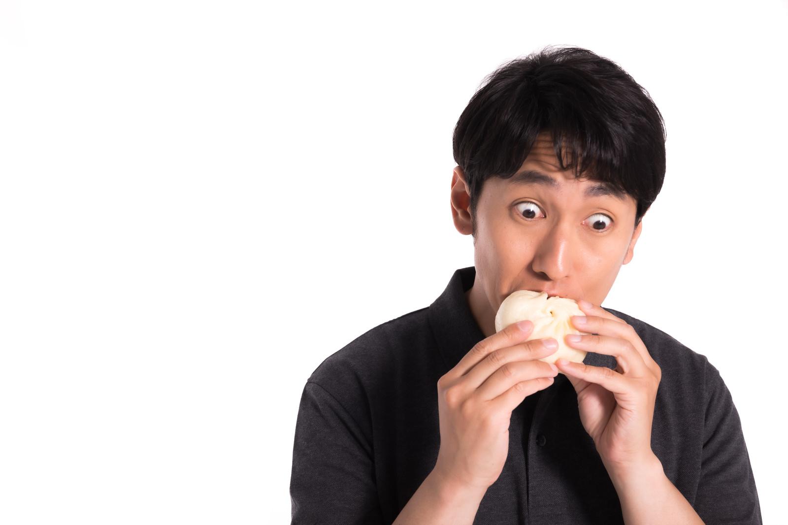 「ジューシーな豚まんに夢中な男性」の写真[モデル:大川竜弥]