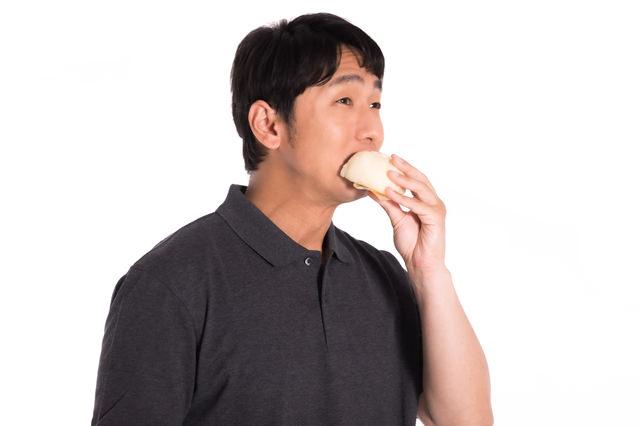片手で豚まんを食べる男性の写真