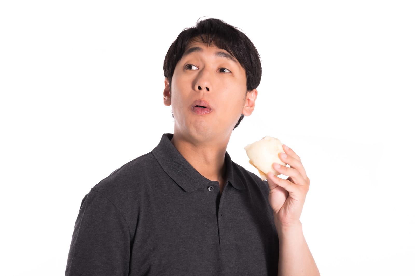 「時間を忘れて豚まんを頬張る男性」の写真[モデル:大川竜弥]