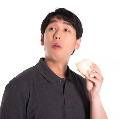 時間を忘れて豚まんを頬張る男性の写真