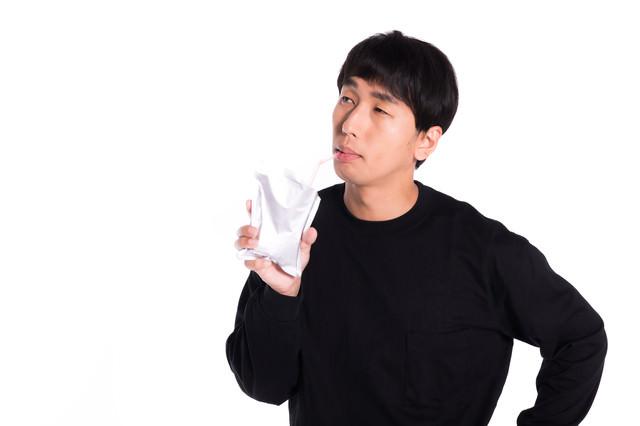 レトルトカレーをストローで吸う男性の写真