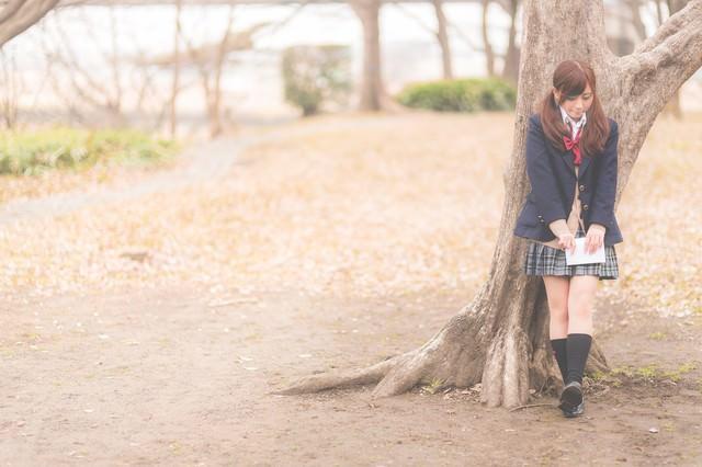 放課後、木陰に隠れて告白のチャンスを伺う女子高生の写真