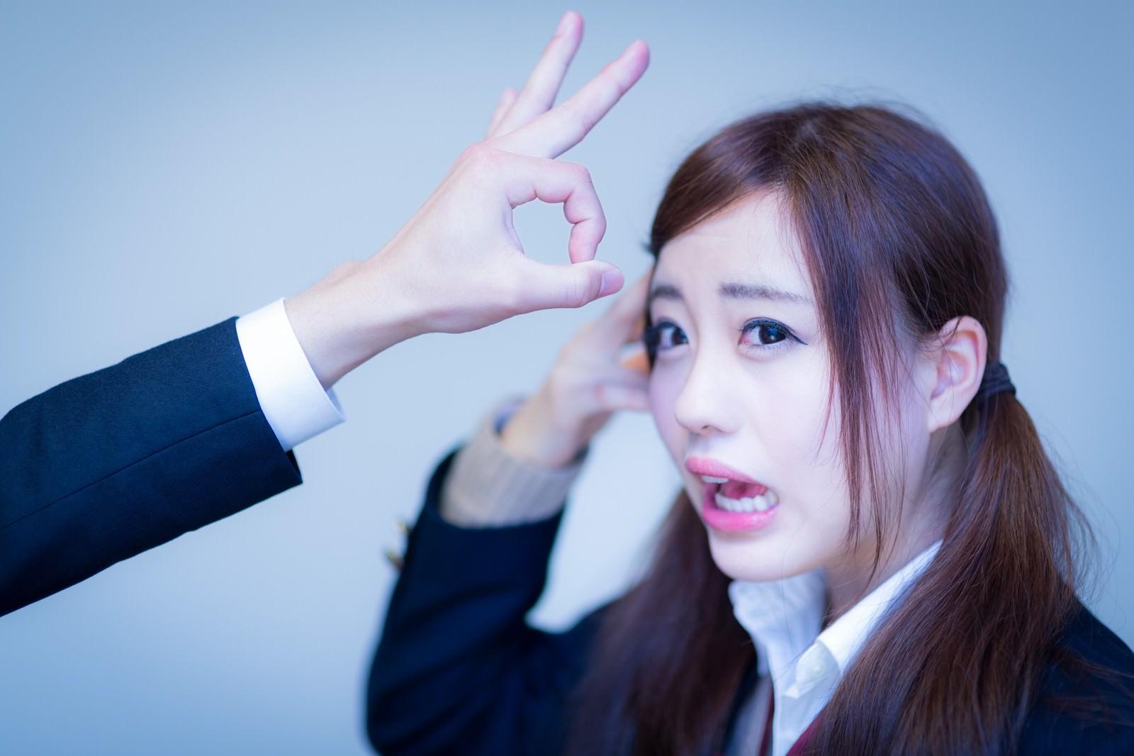 「罰ゲームでデコピンされる女子高生」の写真[モデル:河村友歌]