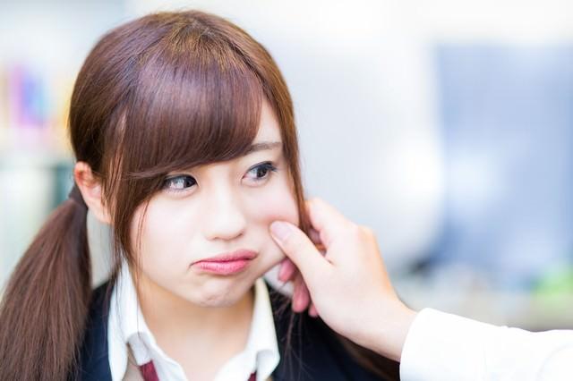 彼氏に頬をつねられる女子高生の写真