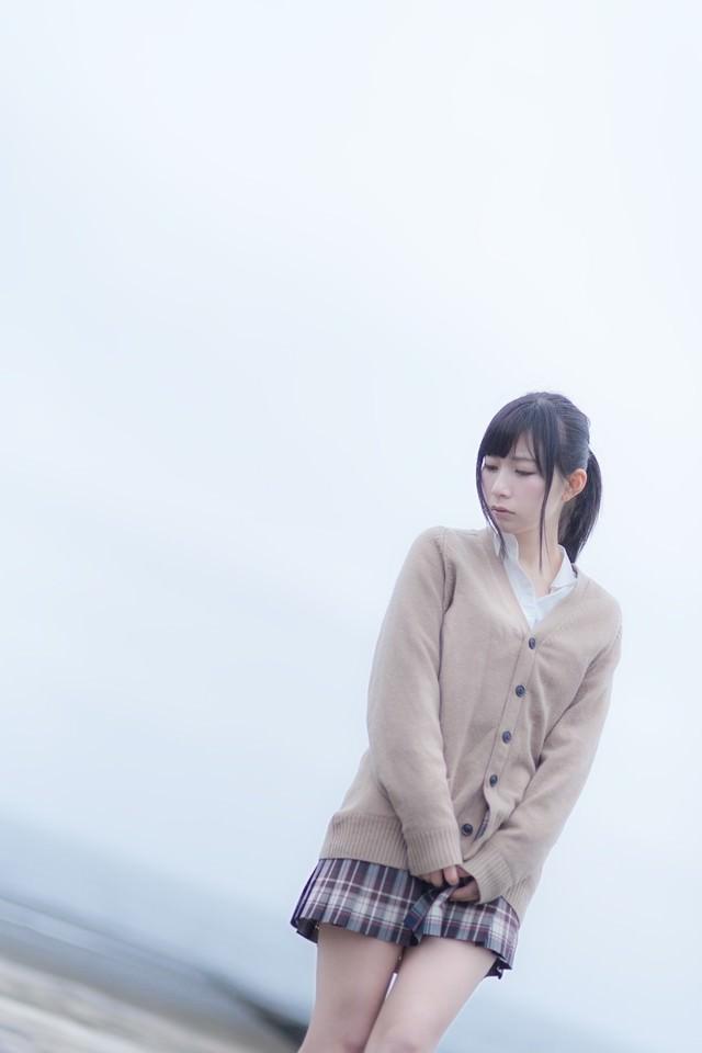 切ない表情で埠頭を歩く女子高生の写真