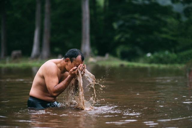 リアルの泥水で洗顔する男性