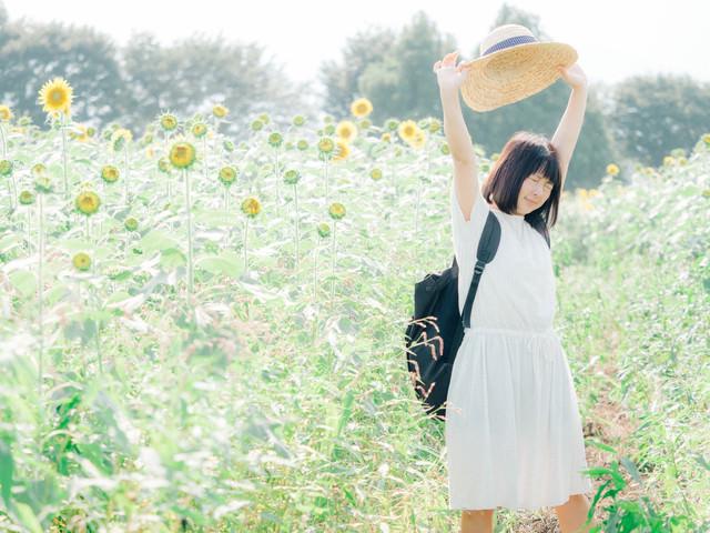 ひまわり畑で伸びをする女性の写真