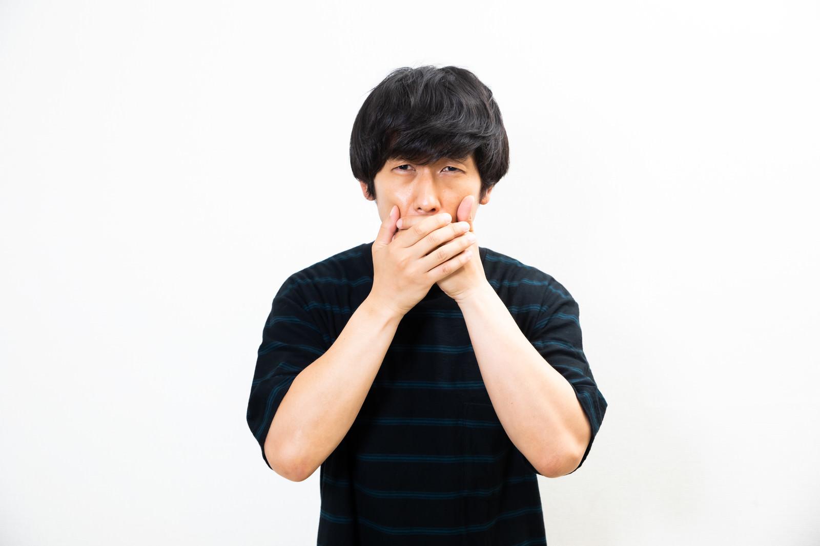 「息苦しさに口を覆う男性」の写真[モデル:大川竜弥]