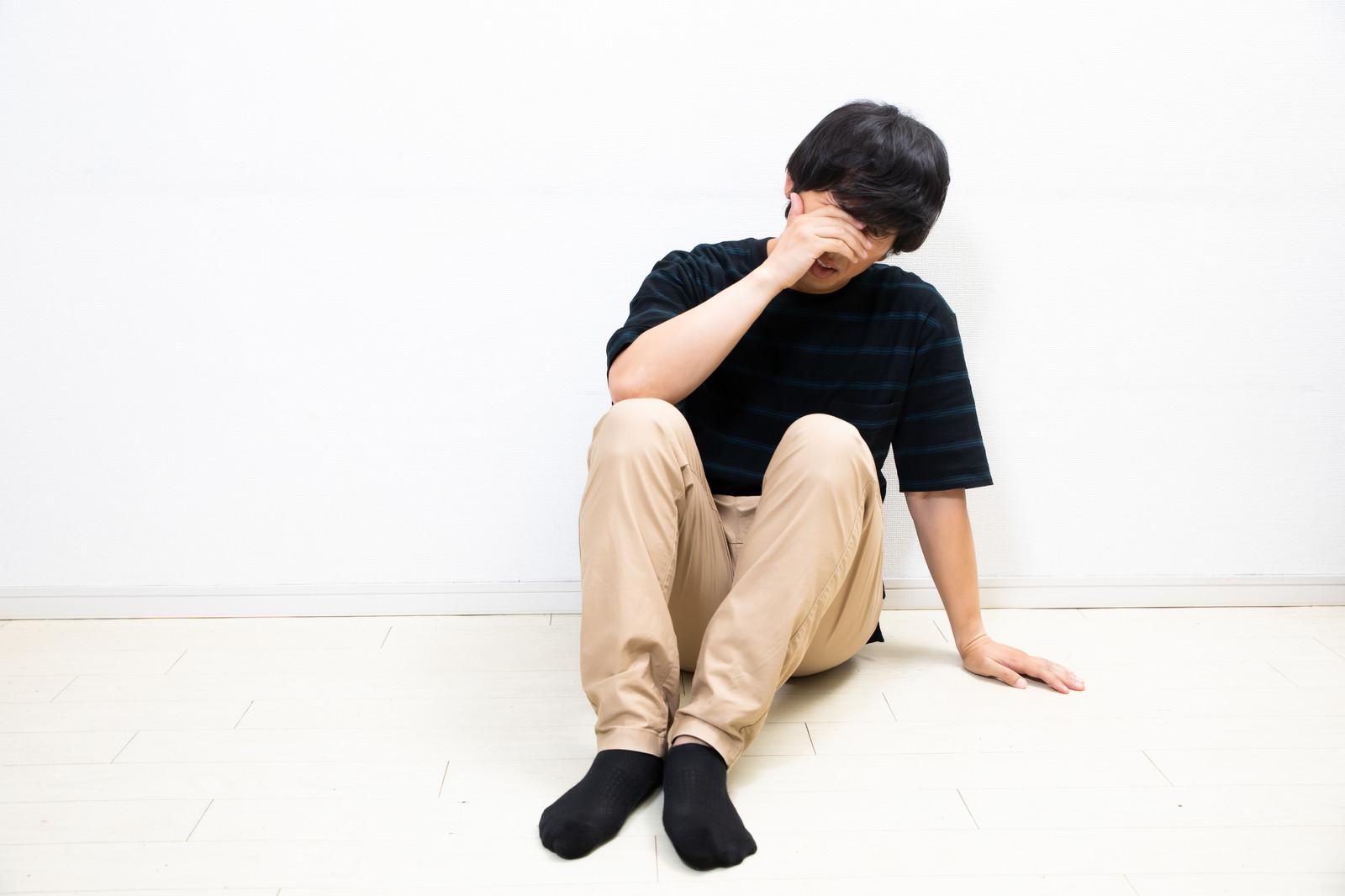 「顔を覆い落ち込む男性」の写真[モデル:大川竜弥]