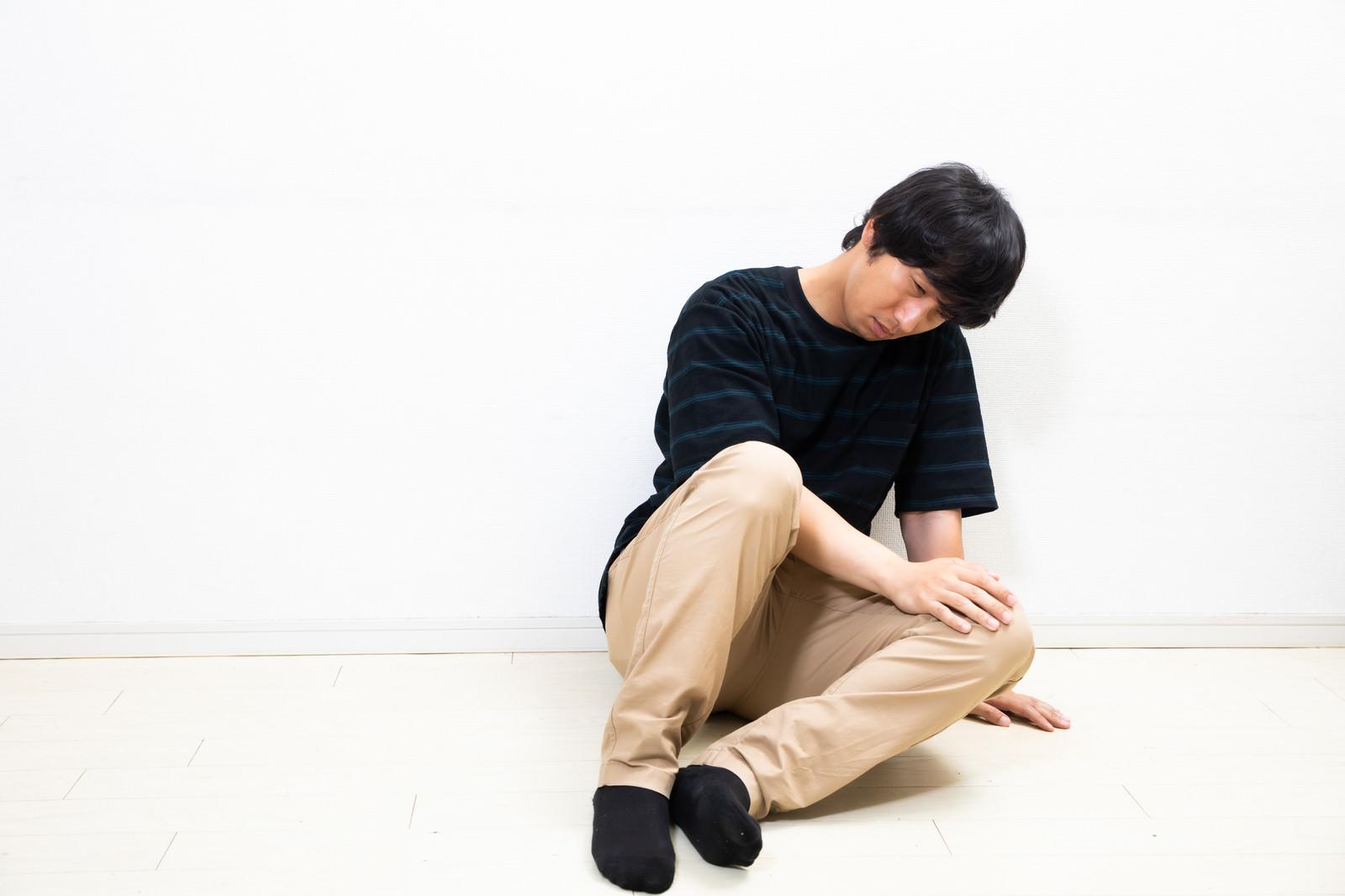 「座り込んでうずくまる男性」の写真[モデル:大川竜弥]