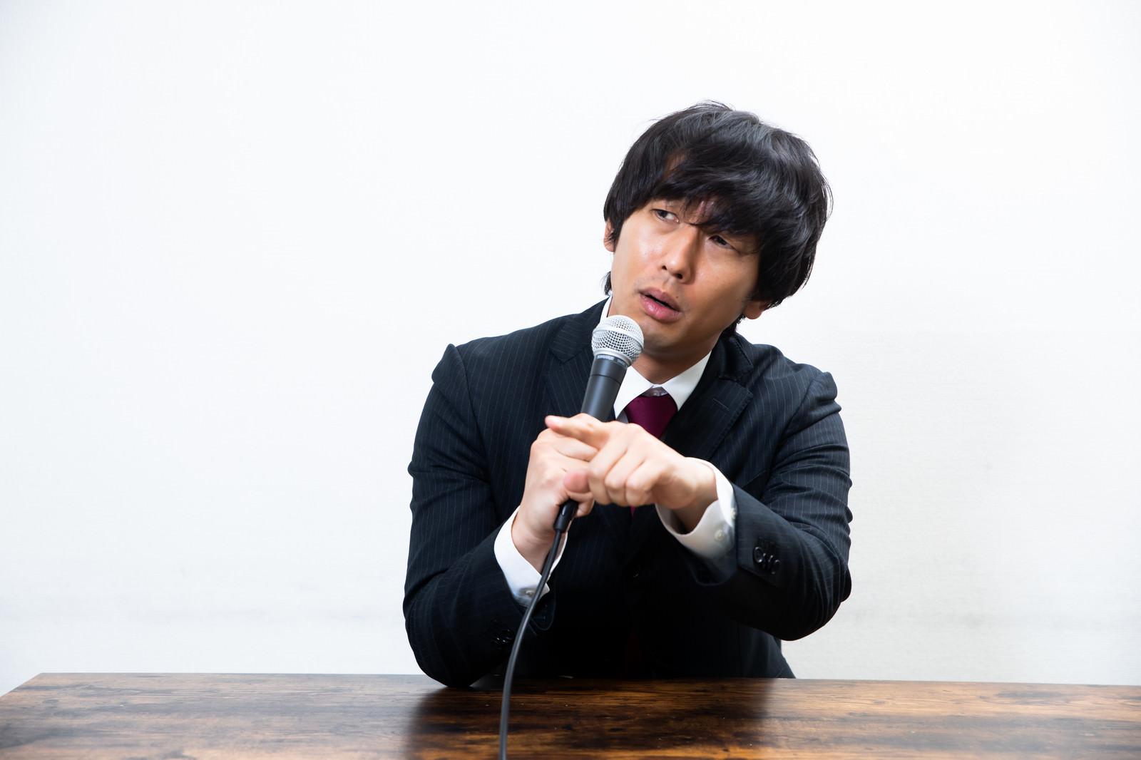 「会見中に質問した記者を煽る男性」の写真[モデル:大川竜弥]