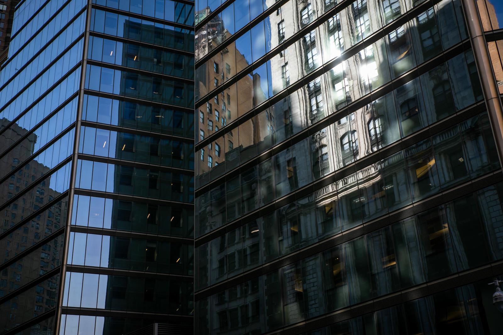 「高層ビルのガラス窓に反射する街並み(ニューヨーク)」の写真
