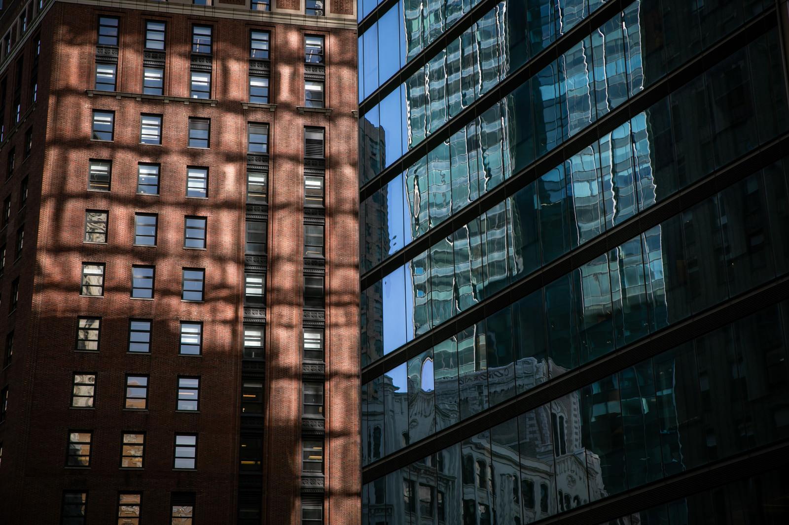 「ガラス張りの窓に映りこむニューヨークの建物」の写真