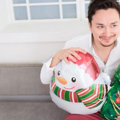「クリスマスグッズを準備して、ガールフレンドが来るのをワクワクしながら待つハーフ」の写真素材
