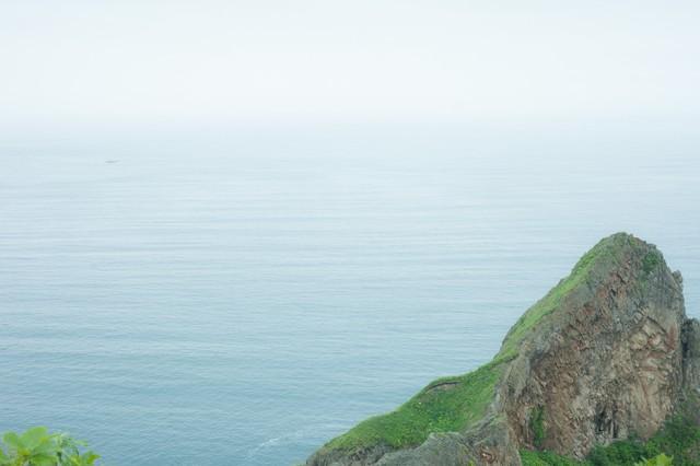 静かな湖畔の岩の影からの写真