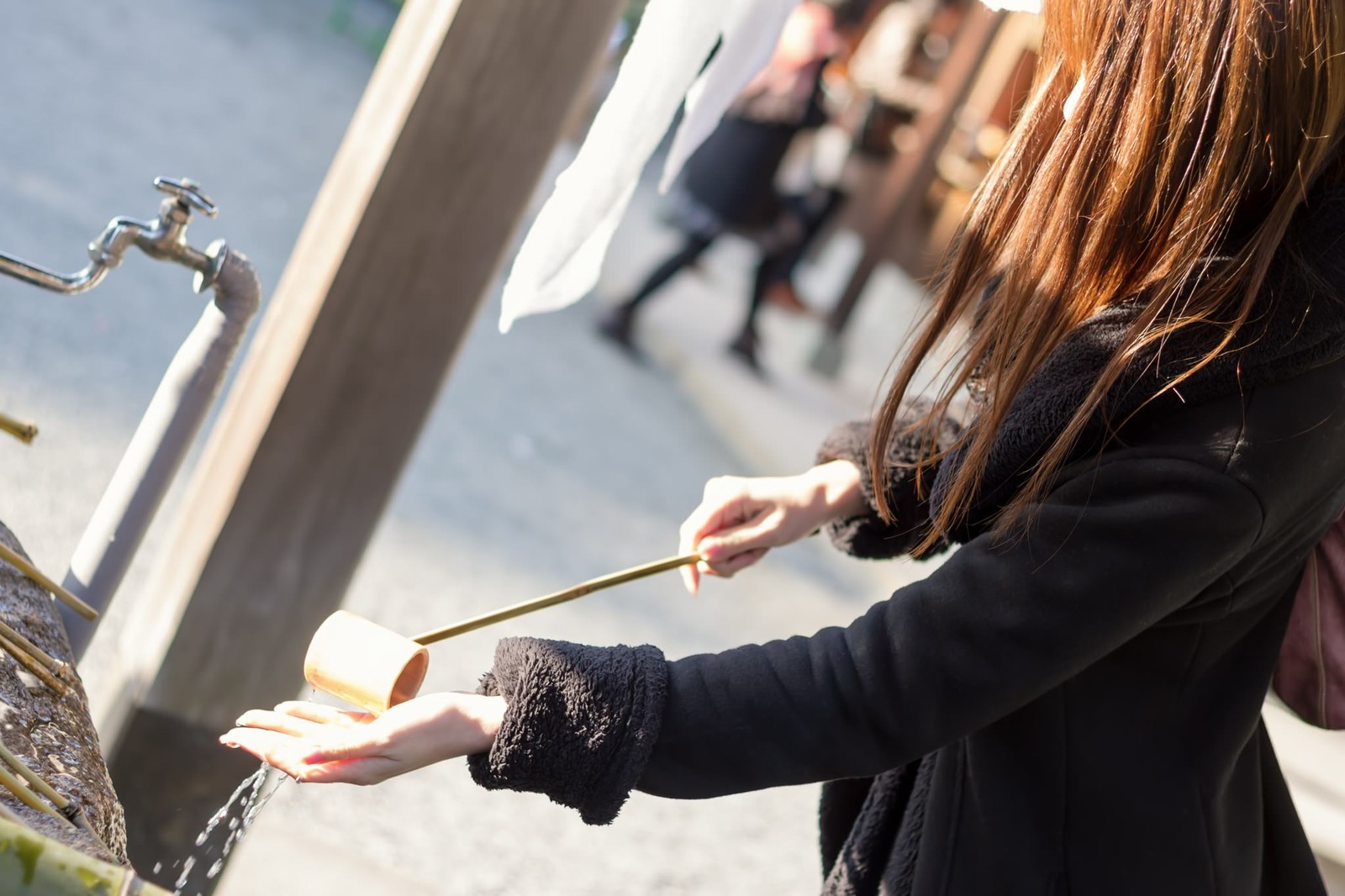 「神社で手水をする女性」の写真