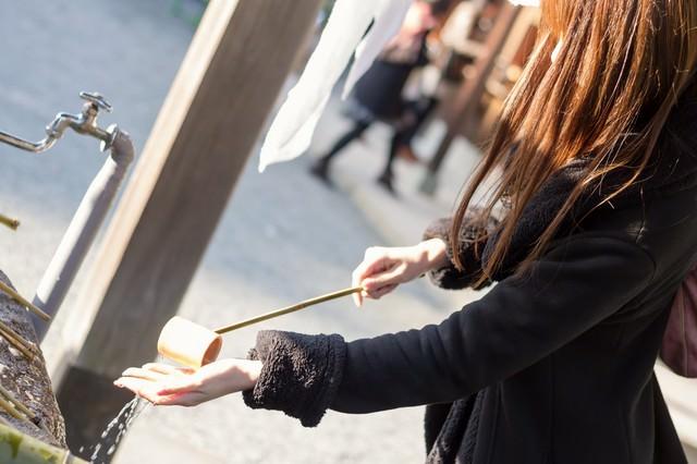神社で手水をする女性の写真
