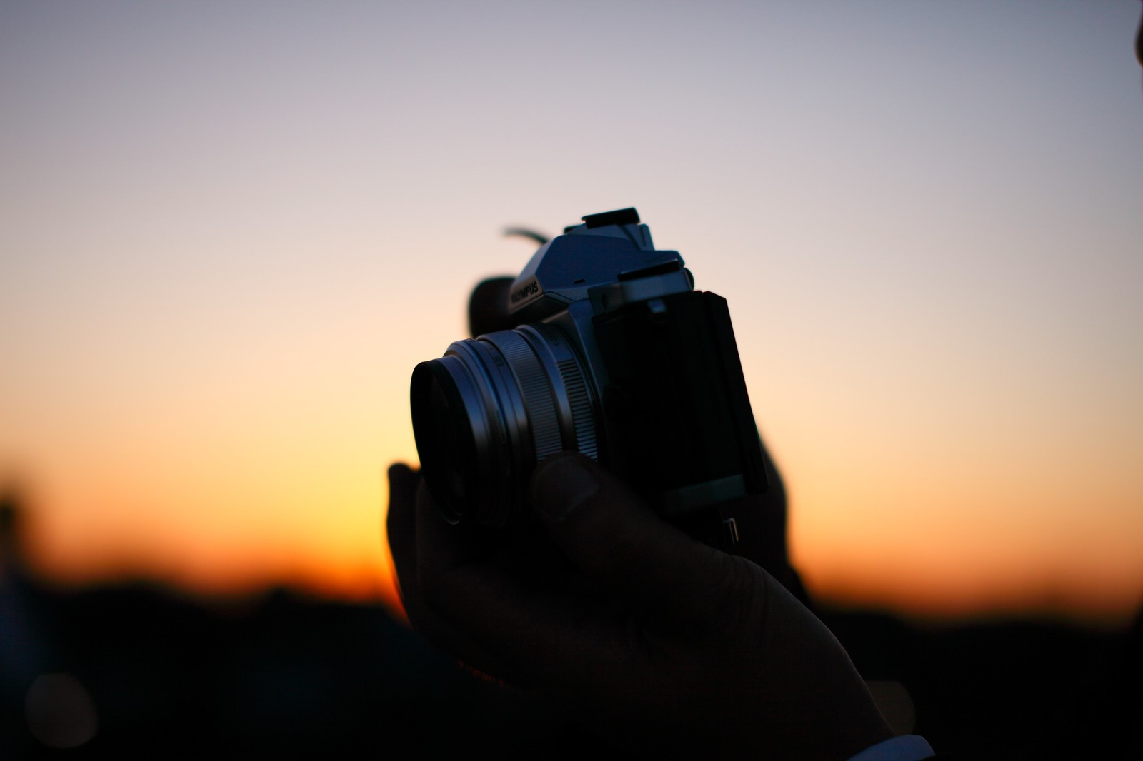「夕焼けに生えるカメラシルエット」の写真
