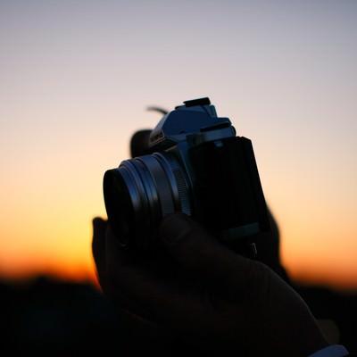 夕焼けに生えるカメラシルエットの写真