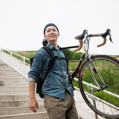 ロードバイクを大事に運ぶ自転車男子の写真