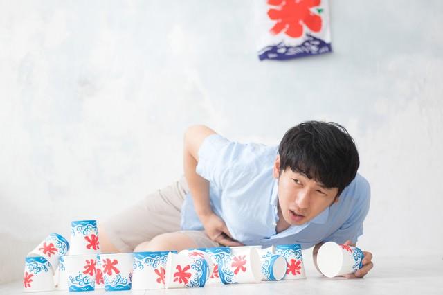 かき氷を食べ過ぎて腹痛を抑えきれない男性の写真