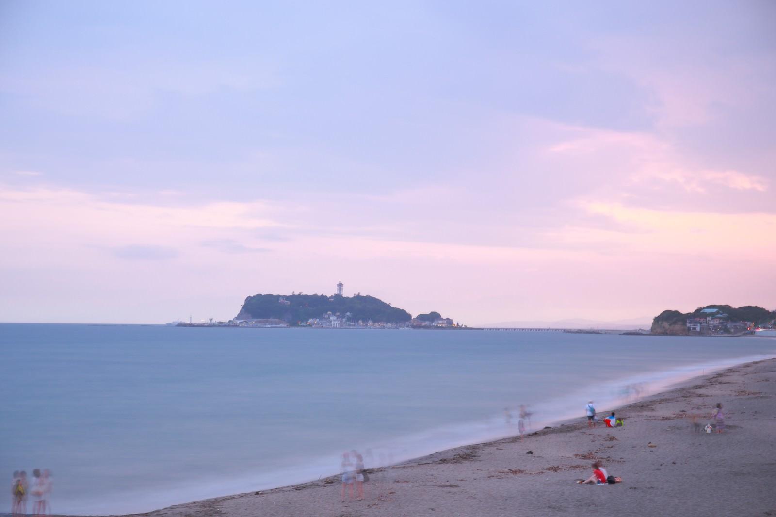 「夕焼けの江ノ島と砂浜で楽しむ人々」の写真