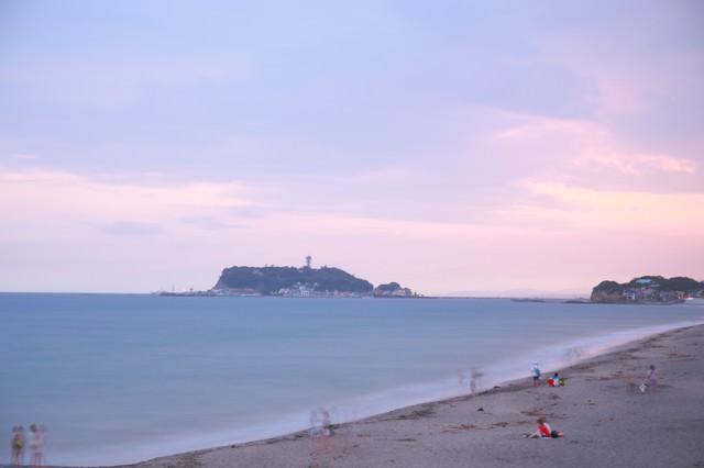 夕焼けの江ノ島と砂浜で楽しむ人々の写真