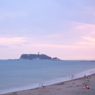 「夕焼けの江ノ島と砂浜で楽しむ人々」の写真素材
