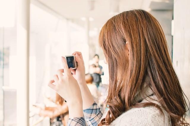 デジカメを持って撮影する女性の写真