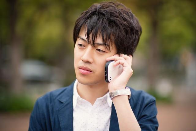 電話で恋人に別れ話を告げられる男性の写真