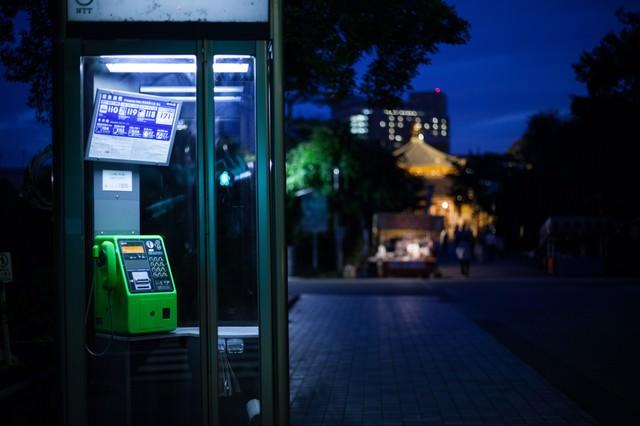 闇夜にてらされる公衆電話の写真