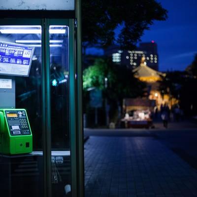 「闇夜にてらされる公衆電話」の写真素材