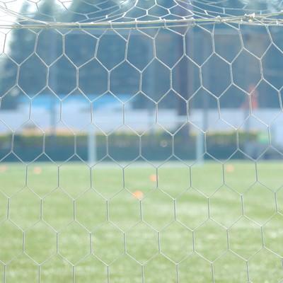 サッカー試合前に静まり返るピッチサイド・ゴールネットの写真