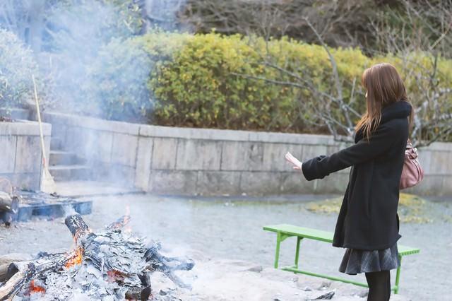 焚火で温まる女性の写真
