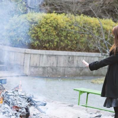 「焚火で温まる女性」の写真素材