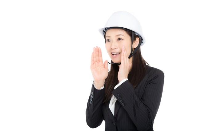 ヘルメットをかぶり声を出す女性の写真