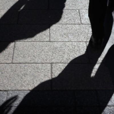 「道路に照らされた忍び寄る影」の写真素材