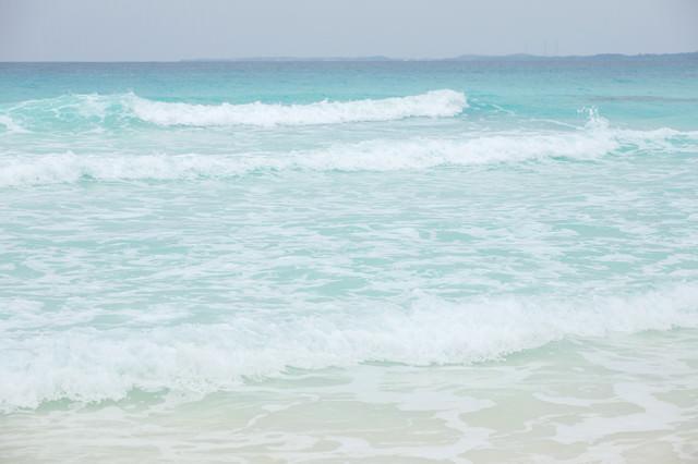 エメラルドグリーンの海と波の写真
