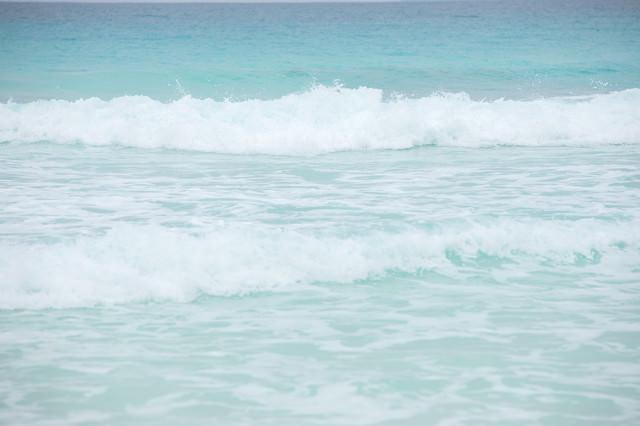 エメラルドの海と波しぶきの写真