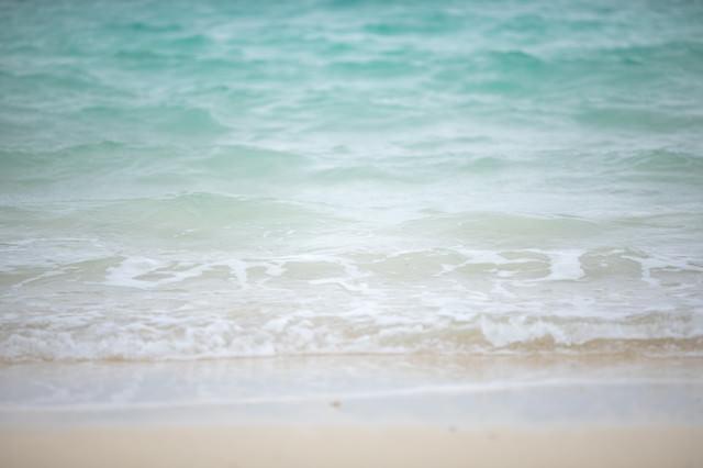 エメラルドグリーンの海と砂浜の写真