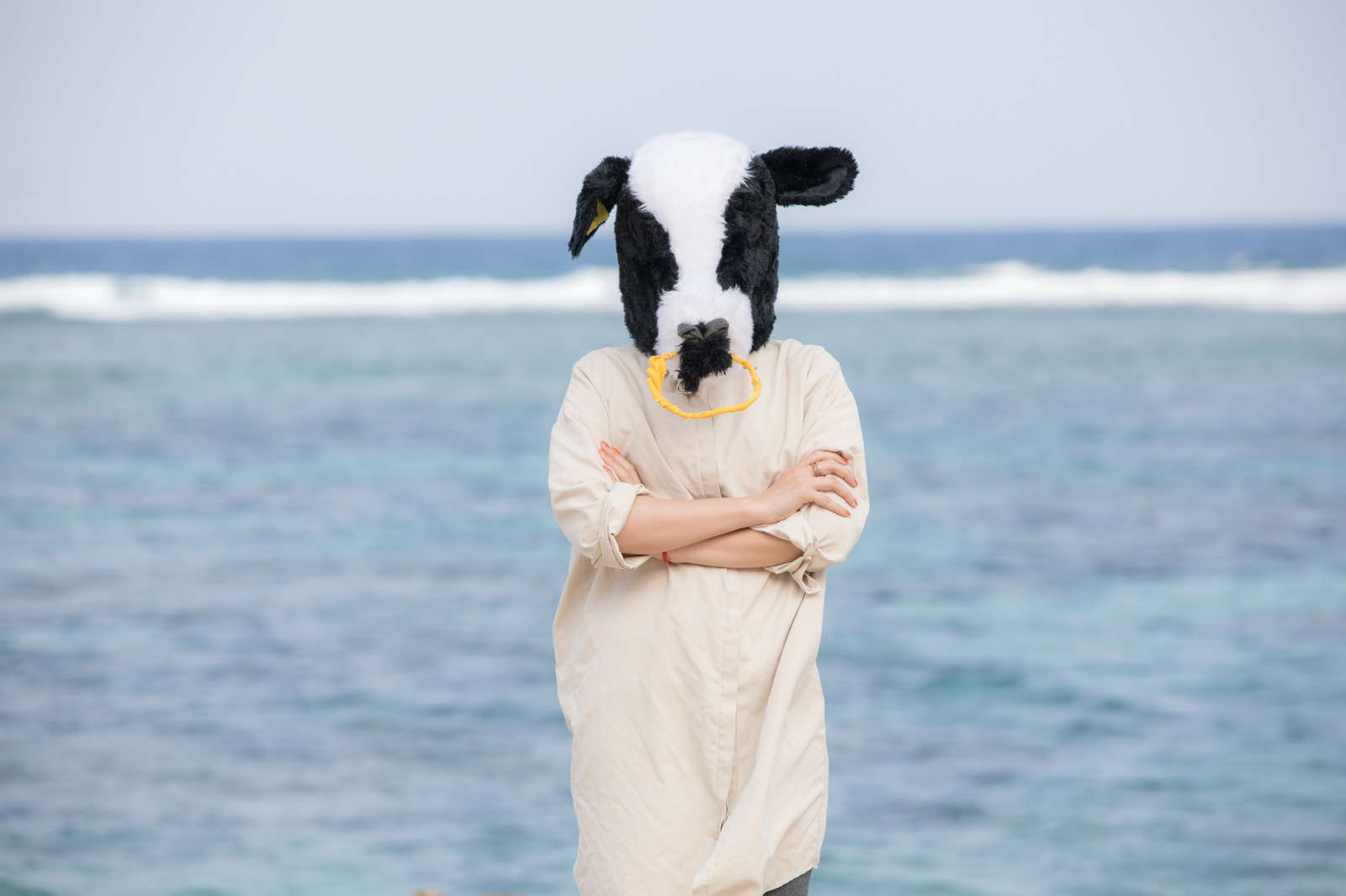 「海を背に腕を組む不気味な牛ガール」の写真[モデル:古性のっち]