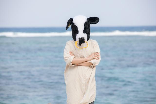 海を背に腕を組む不気味な牛ガールの写真